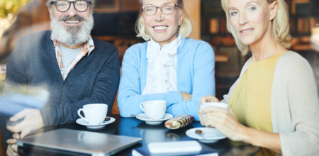 Three happy seniors in smart casual looking at you while sitting by table and relaxing after tea-time
